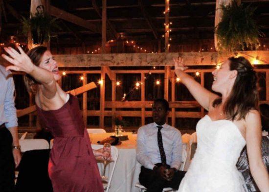 Bride and bridesmaid dancing and laughing at a barn wedding