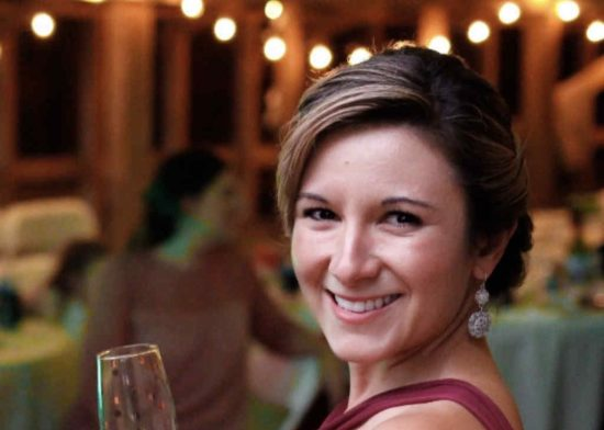 Smiling bridesmaid with a wine glass at a barn wedding reception in Eldon, Missouri